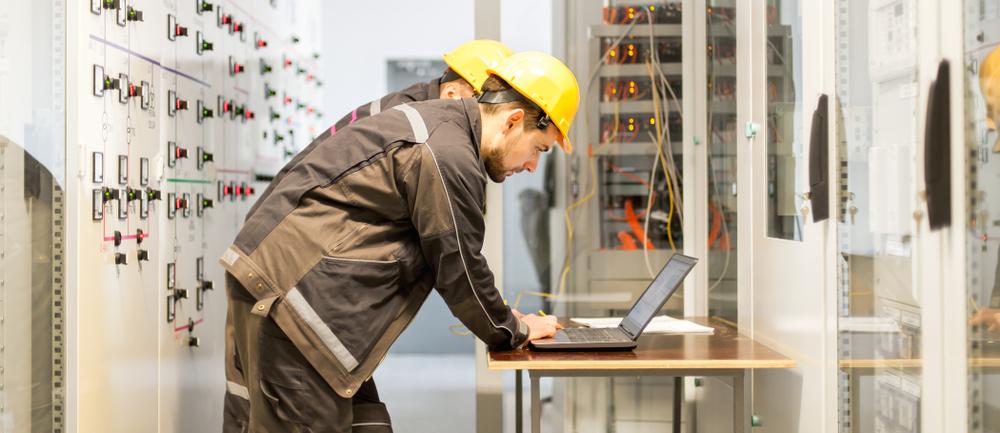 dois homens realizando serviços de engenharia elétrica com notebook